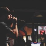 A man in a Deep Ellum bar sings through a microphone held close to his face