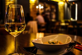 A glass of white wine sits next to a bowl of food on a wood table