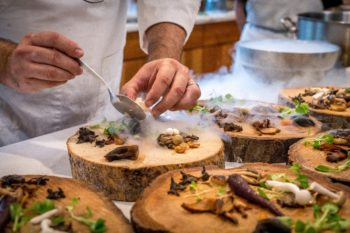 A chef plats appetizers onto a wood block