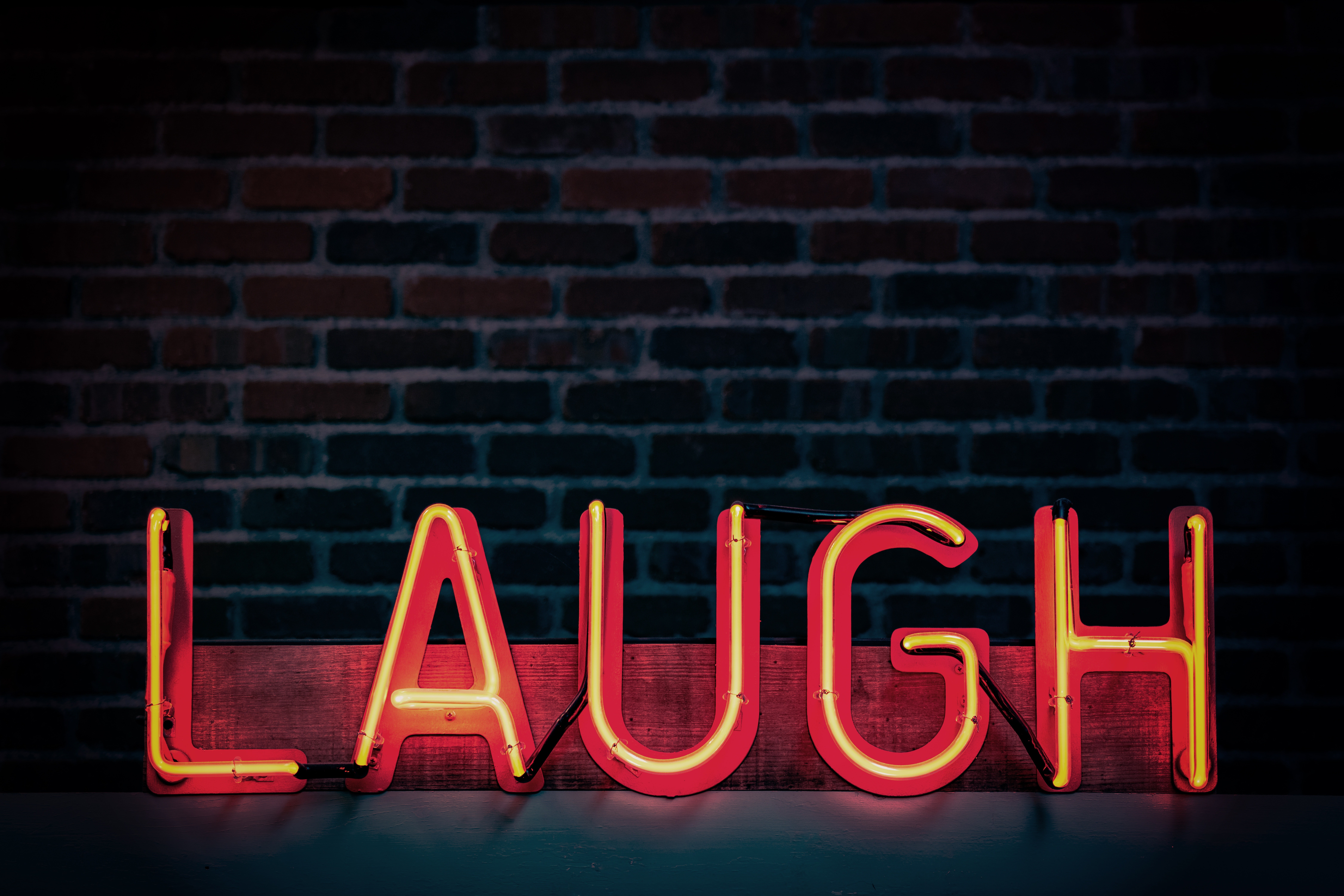 "A red and yellow neon sign that reads ""laugh"""