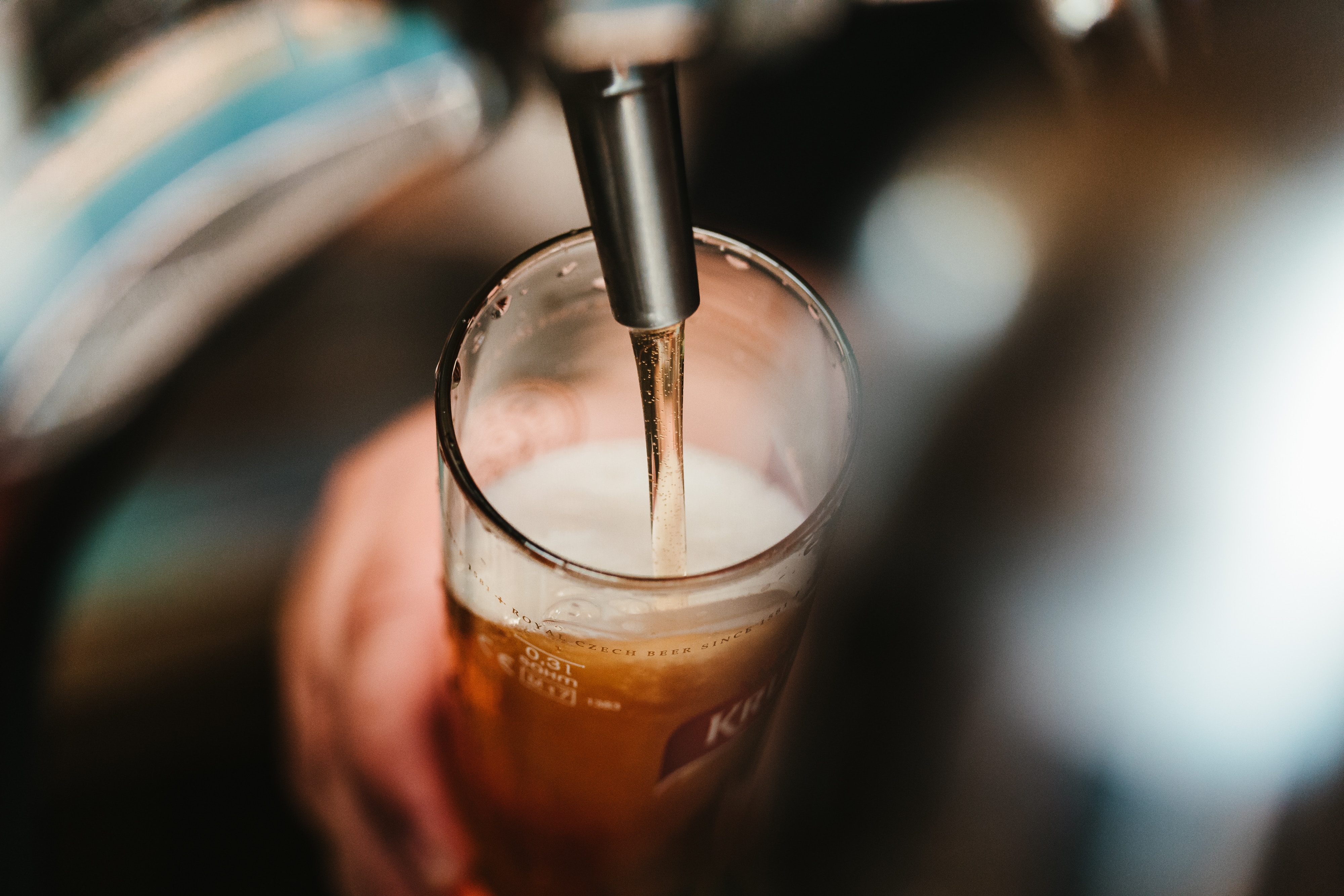 A bartender filling a glass of beer on tap