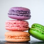 Purple, pink, orange, and green macarons stacked on top of each other
