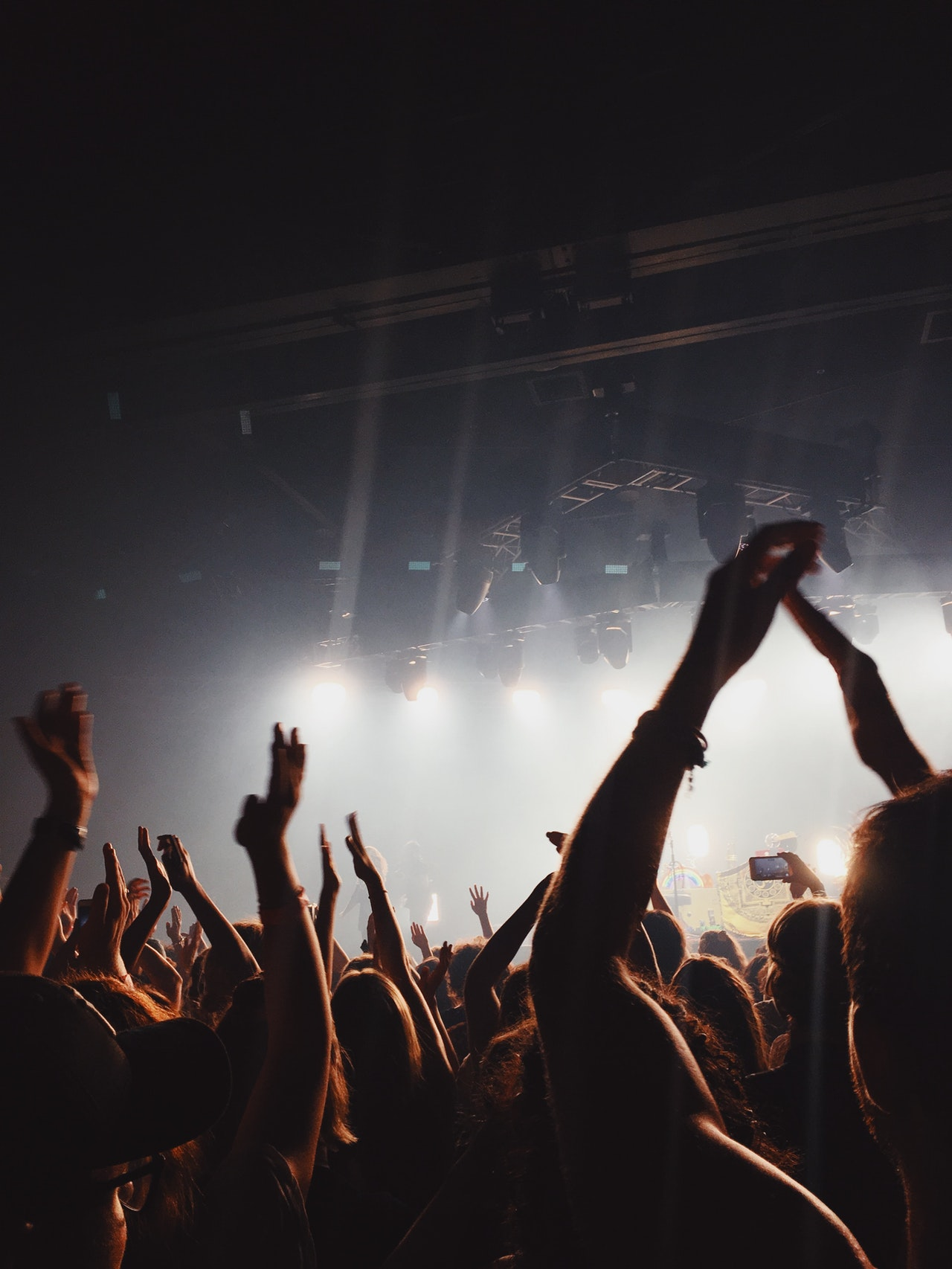 Fans raise their hands in air at a music venue.
