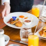A waiter serves a plate of food on a table with orange juice and brunch condiments.