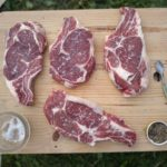 Four rib eye steaks with marbling sit on a cutting board.