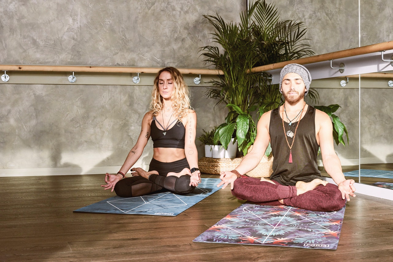 Two people do yoga poses on mats in a studio.