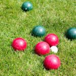 red and green bocce balls in the grass