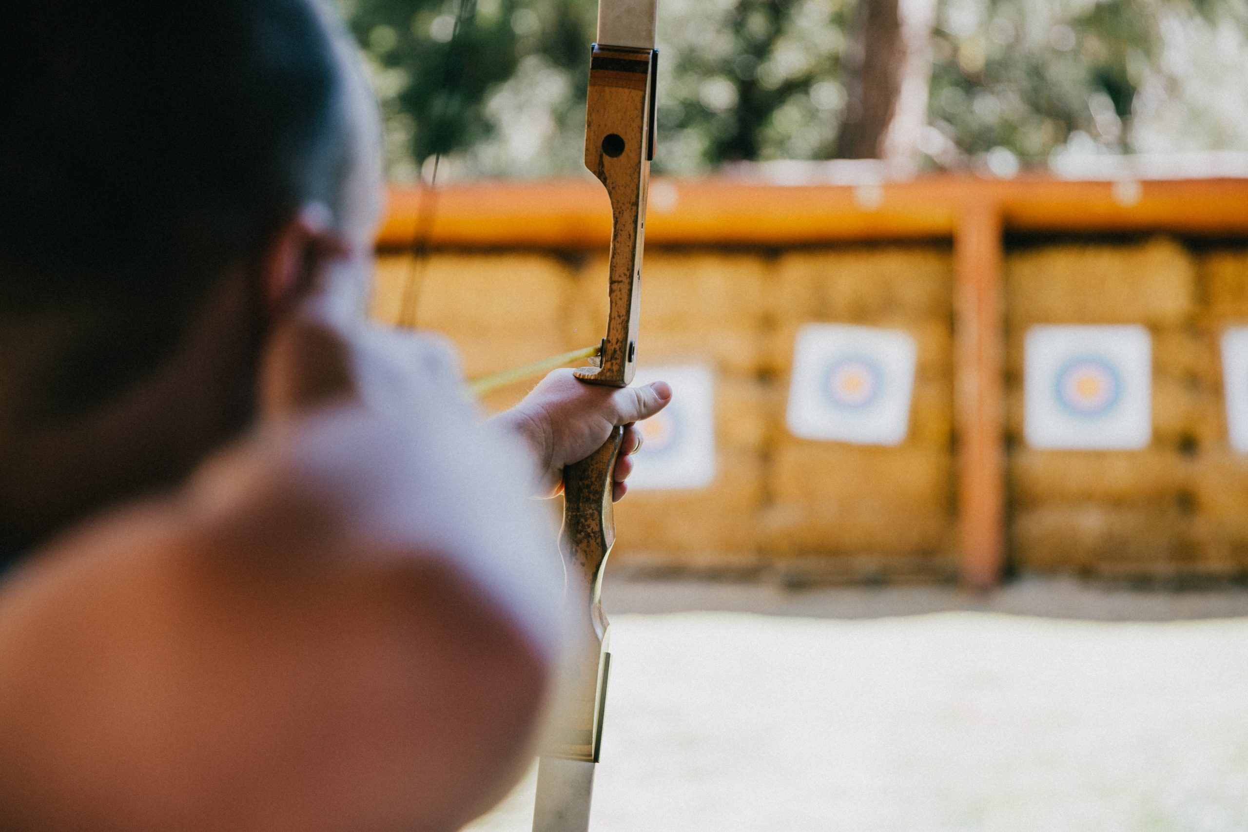 A close-up of someone shooting an arrow at a target at an archery range.