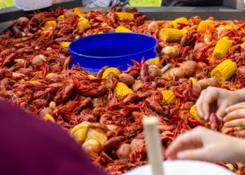A table full of crawfish, corn, and potatoes at a Cajun restaurant