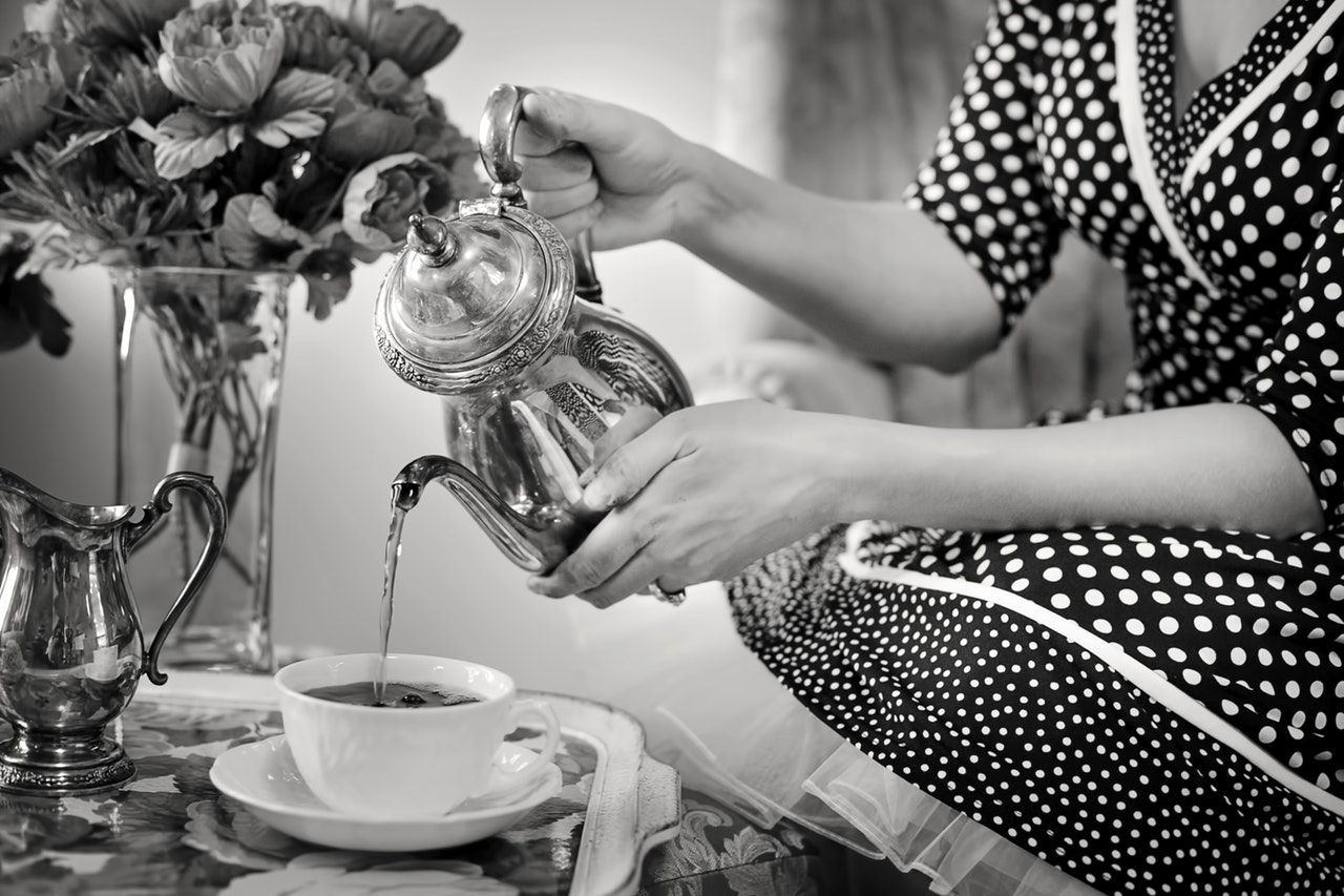 Greyscale photo of woman pouring tea