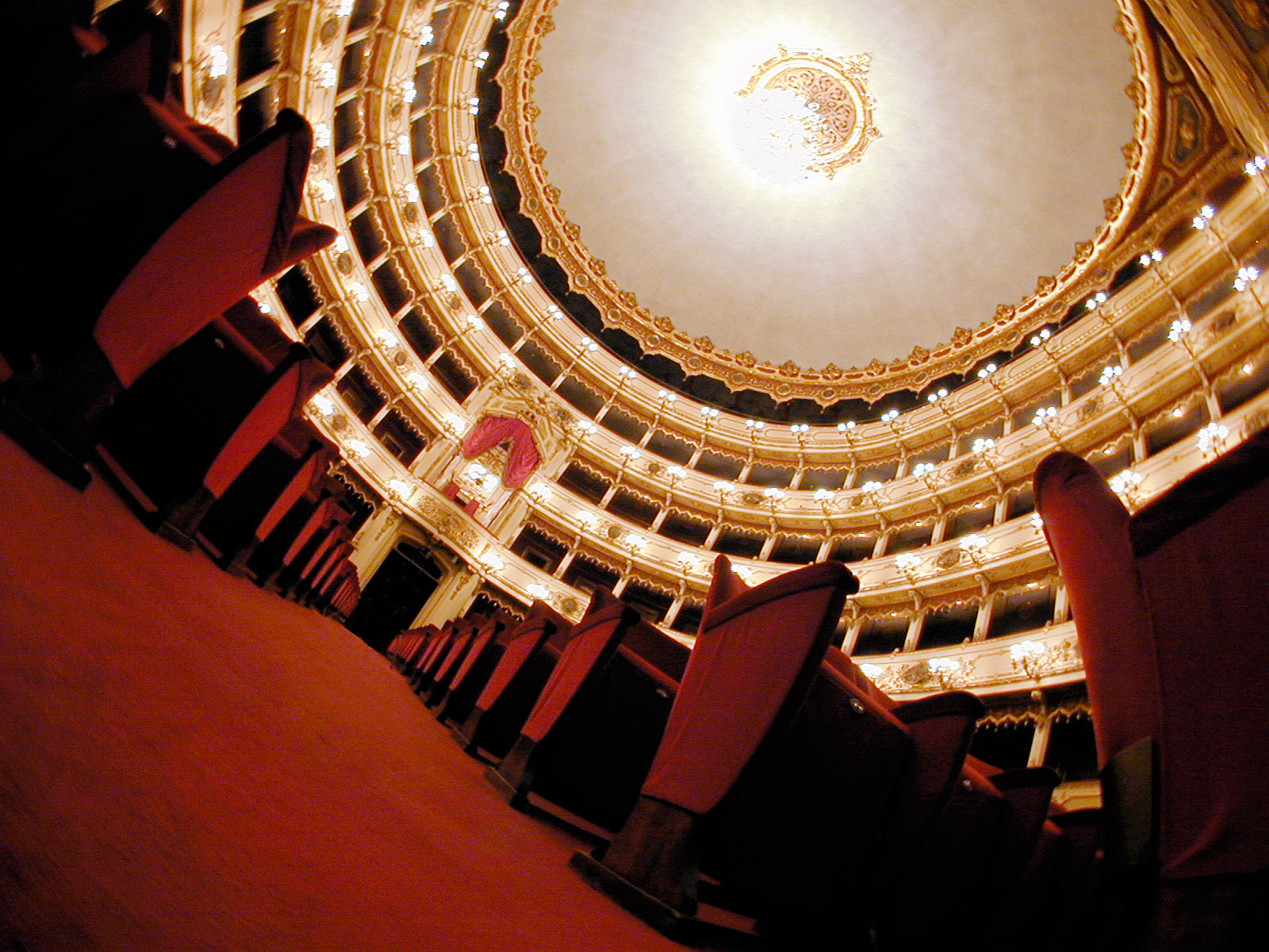 A view of a theater's domed ceiling. Red velvet chairs line the sides.