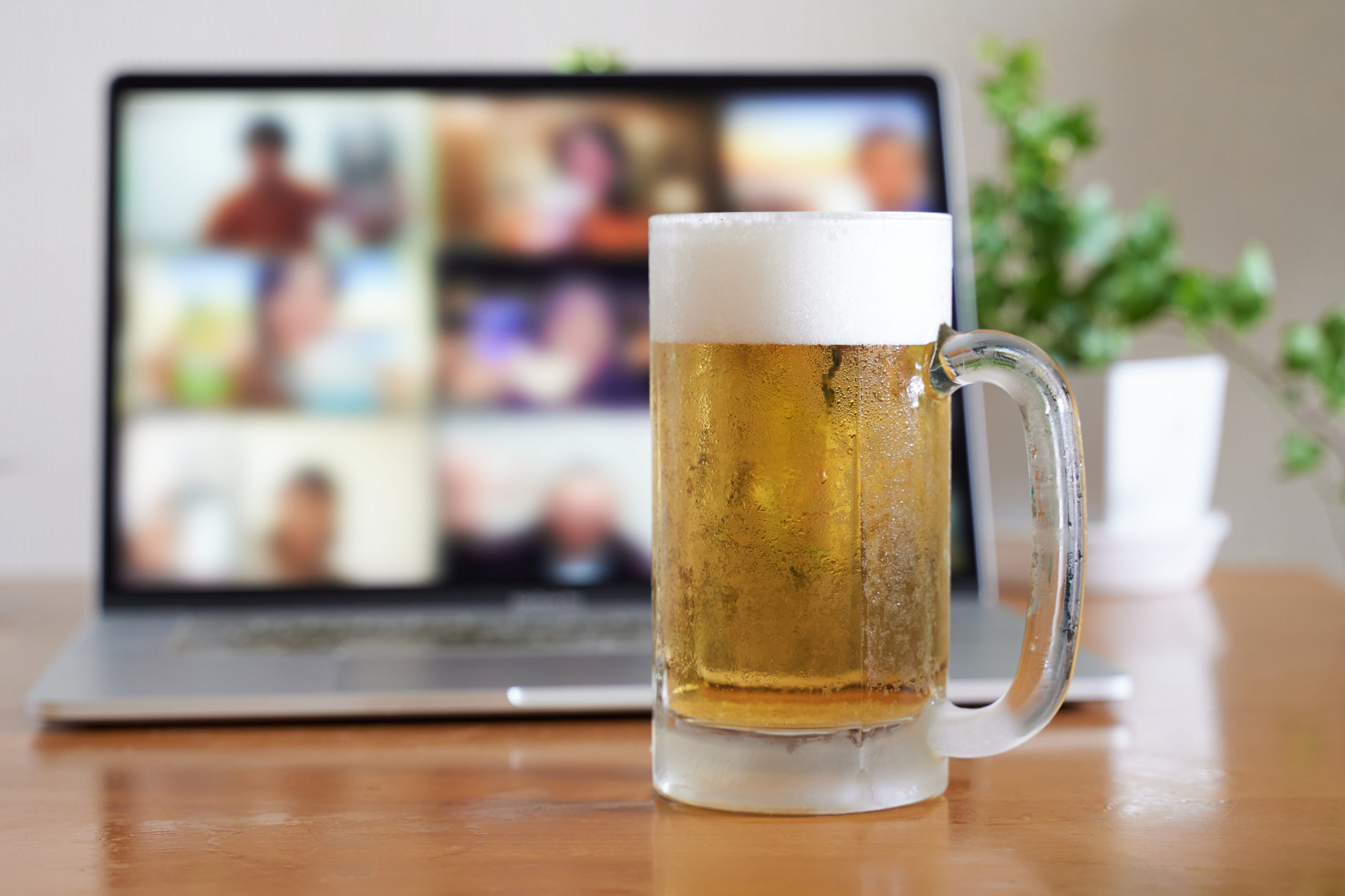 A mug of beer sits in front of a laptop on a table.