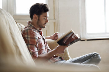 A man reads on a white couch.