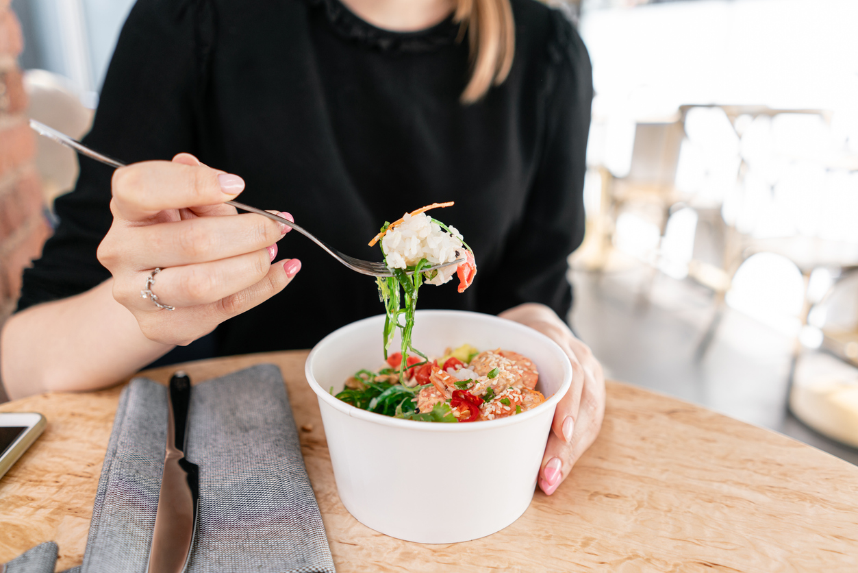 A woman eats a bowl of poke at a table