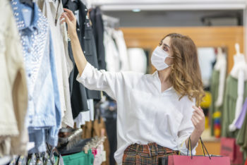 A woman wearing a mask shops in a clothing store.