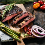 Sliced steak and vegetables on a stone slab