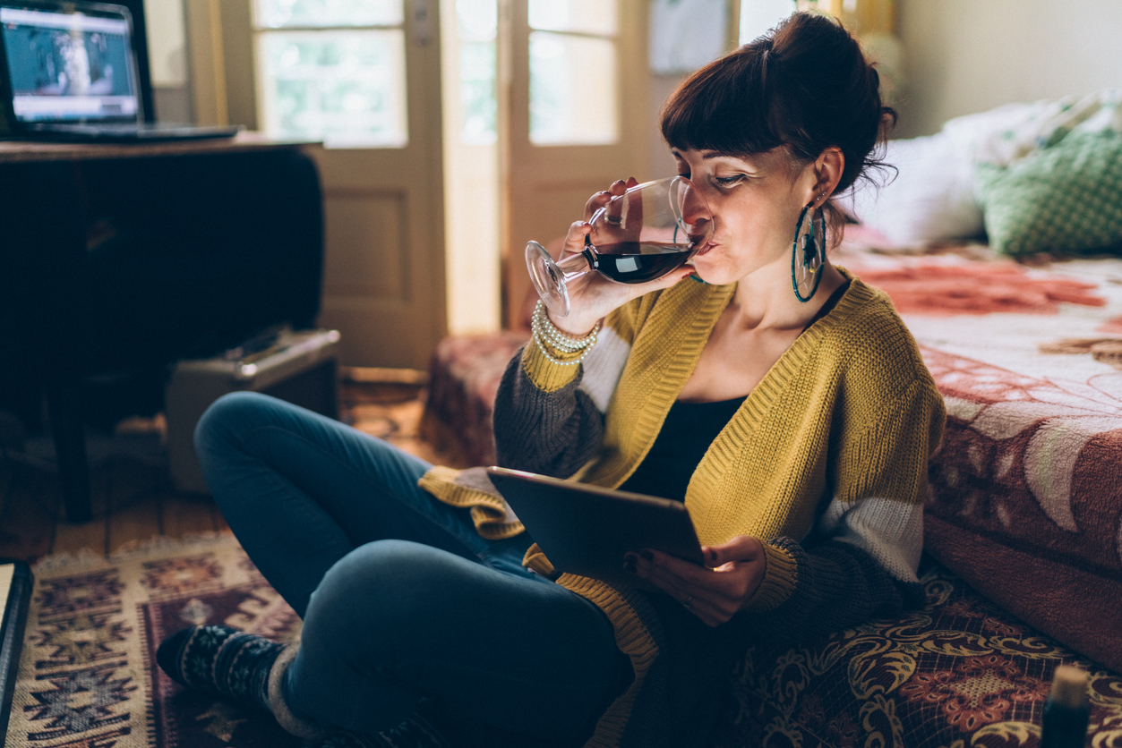 A woman sits on the floor drinking wine and reading from a tablet.
