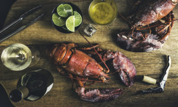 a lobster dinner spread out on a wood table