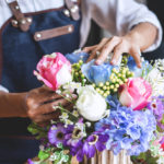 A florist's hands can be seen arranging a bouquet