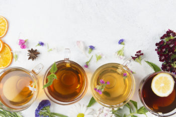 A row of glass tea cups on a white table, surrounded by flowers.