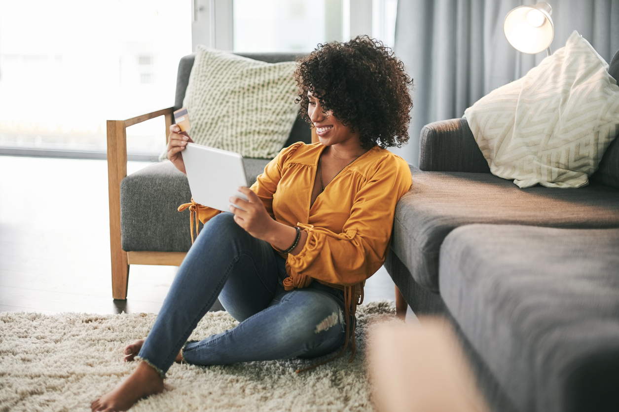 A woman sits on the floor in front of her couch, using her debit card to purchase something on her tablet.