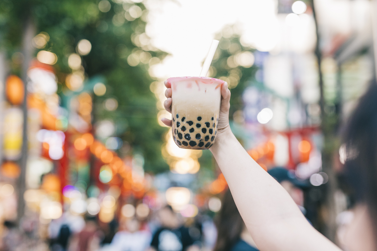 A hand holds up a cup of boba tea on a street.