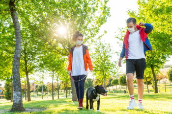 A couple wearing masks walk their dog in a park on a sunny day -dog parks in Dallas