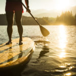A person backlit by the setting sun on a paddleboard in the middle of a lake - Dallas watersports