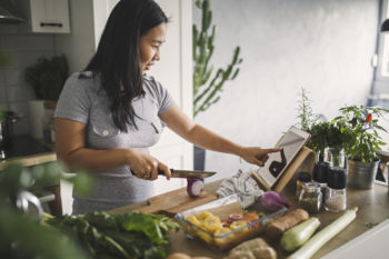 A woman follows along to a tablet while cooking at home.