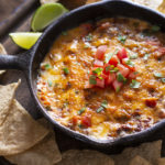 A skillet of queso cheese on a table - queso in Dallas